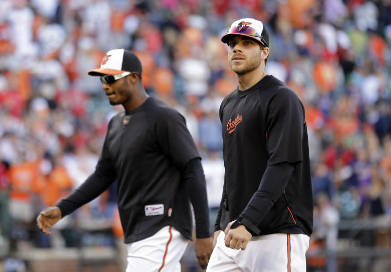 Baltimore Orioles' Chris Davis, right, walks off the field with teammate Adam Jones after a baseball game against the Boston Red Sox, Sunday, Sept. 29, 2013, in Baltimore. Davis left the game in the fourth inning and did not return after spraining his wrist on a play at first base. (AP Photo/Patrick Semansky)