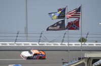 FILE - In this July 4, 2015, file photo, U.S., Confederate and Dale Earnhardt Sr. and Jr. flags fly near Turn 4 during NASCAR qualifying at Daytona International Speedway in Daytona Beach, Fla. A predominantly white sport with deep Southern roots and a longtime embrace of Confederate symbols, NASCAR was forced last summer to face its own checkered racial history during the country's social unrest. (AP Photo/Phelan M. Ebenhack, File)