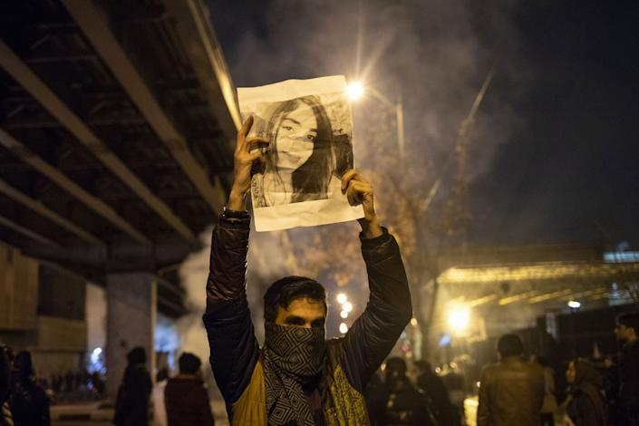 Iranian man holds a picture of a victim of the Ukrainian Boeing 737-800 plane crash during a demonstration in front of Tehran's Amir Kabir University: AFP via Getty Images