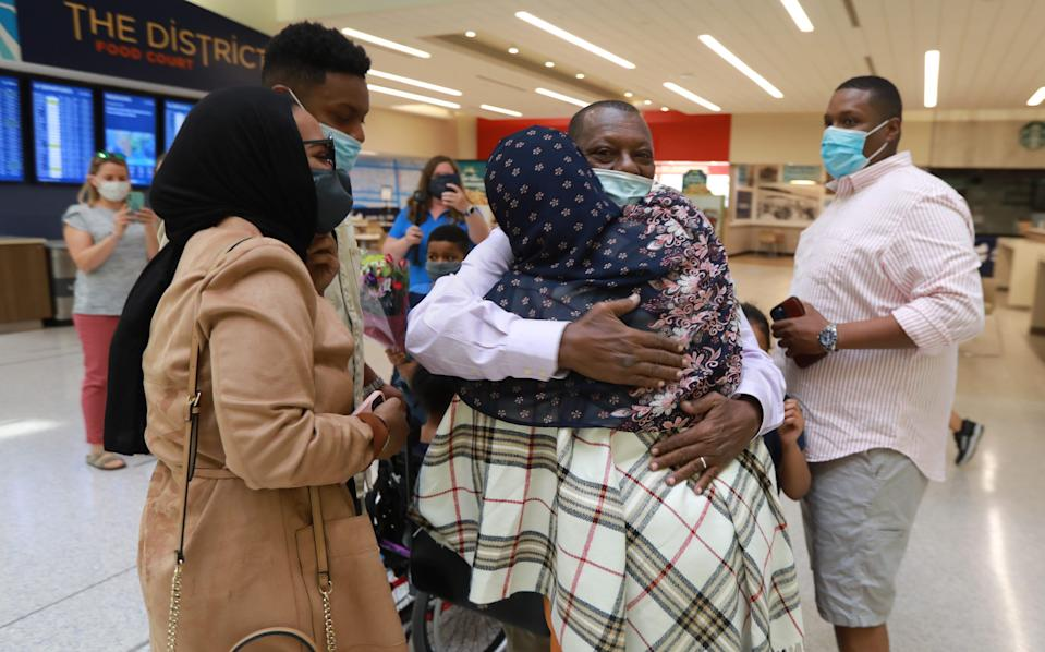 Mohamed Salem Ali gets a hug from wife Fadumo Hussien shortly after he arrived at John Glenn International Airport on April 8, 2021. Ali, a Somali man living in Malaysia, wasn't able to come for three years to join his family in Columbus due to Trump's Muslim ban. When Biden lifted the ban earlier this year, the family got their father a visa and he arrived in Columbus Thursday morning, April 8, 2021.