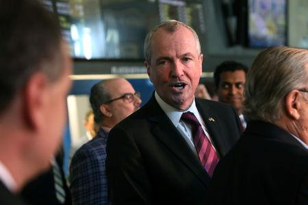 New Jersey Governor Phil Murphy speaks to a colleague before placing the first legal sports bets in the State of New Jersey at Monmouth Park Sports Book by William Hill, on the opening of the first day of legal betting on sports in Oceanport, New Jersey, U.S., June 14, 2018. REUTERS/Mike Segar