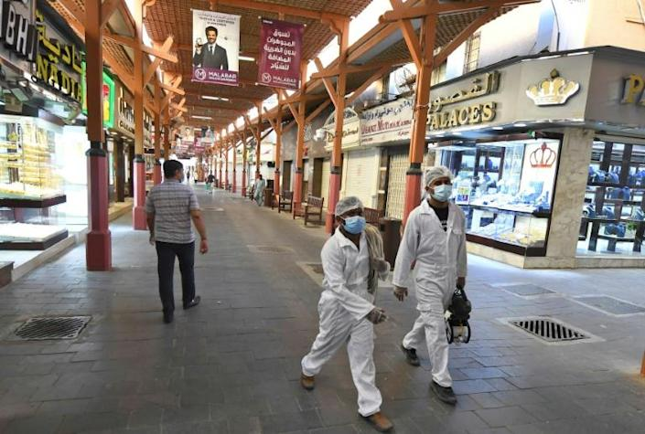 Workers in protective clothing carry sterilisation gear at the Dubai Gold Souk (AFP Photo/Karim SAHIB)