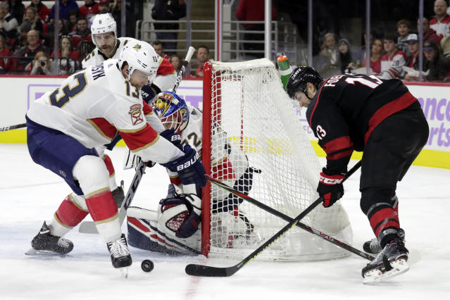 Carolina Hurricanes' Warren Foegele (13) has his shot stopped by Florida Panthers' Mark Pysyk (13) and Sergei Bobrovsky (72), of Russia, during the second period of an NHL hockey game in Raleigh, N.C., Saturday, Nov. 23, 2019. (AP Photo/Chris Seward)