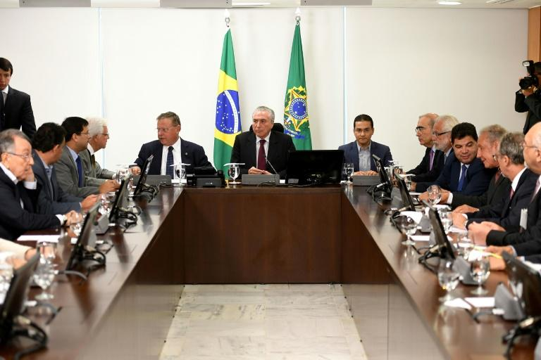 Brazilian President Michel Temer (C), flanked by his Agriculture Minister Blairo Maggi (L) and Industry and External Commerce Minister Marco Pereira, holds an emergency meeting with meatpacking representatives