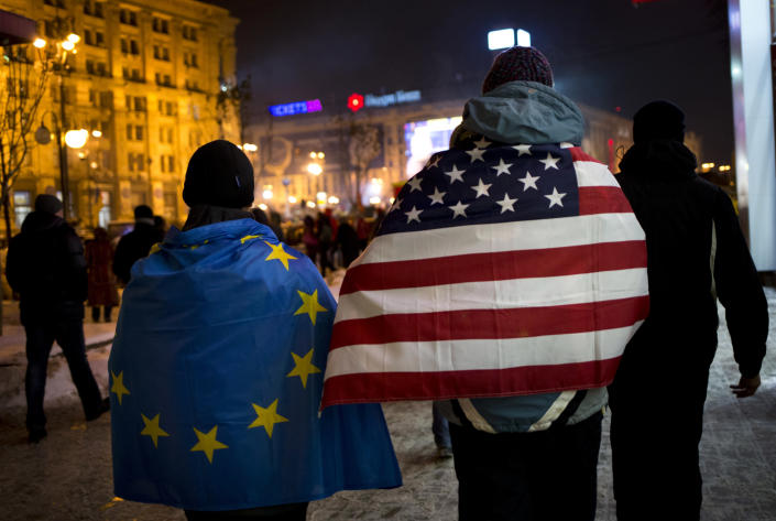 Pro-European Union activists wearing EU and U.S. national flags walk through the Independence Square in Kiev, Ukraine, Wednesday, Dec. 11, 2013. Opposition leaders in Ukraine rejected President Viktor Yanukovych's offer of talks Wednesday, saying they will not sit down with him until he fires his government and releases all arrested demonstrators. (AP Photo/Alexander Zemlianichenko)