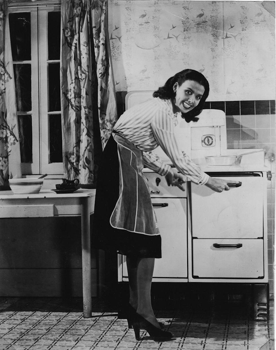 <p>The singer and actress checks on the meal that's cooking in her oven while in her kitchen in 1940. </p>