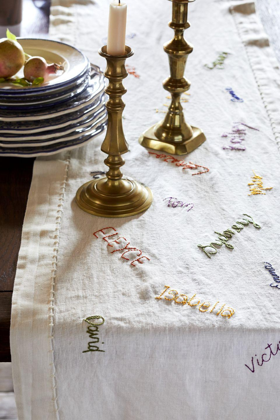 """<p>Want to make everyone in the family feel loved? Create a table runner with each guest's name stitched right on it. Use disappearing ink pens to write the names before embroidering them on for homespun decoration. What a fun alternative to <a href=""""https://www.countryliving.com/entertaining/g1538/diy-place-cards/"""" rel=""""nofollow noopener"""" target=""""_blank"""" data-ylk=""""slk:place cards"""" class=""""link rapid-noclick-resp"""">place cards</a>!</p><p><a class=""""link rapid-noclick-resp"""" href=""""https://www.amazon.com/Dritz-677-60-Disappearing-Marking-Purple/dp/B00175Z2QE/?tag=syn-yahoo-20&ascsubtag=%5Bartid%7C10050.g.1371%5Bsrc%7Cyahoo-us"""" rel=""""nofollow noopener"""" target=""""_blank"""" data-ylk=""""slk:SHOP DISAPPEARING INK PENS"""">SHOP DISAPPEARING INK PENS</a></p>"""