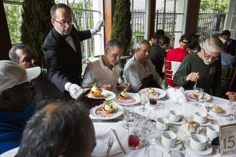 A waiter serves dessert to a table of men listening to Chinese millionaire Chen Guangbiao during a lunch he sponsored for hundreds of needy New Yorkers at Loeb Boathouse in New York's Central Park