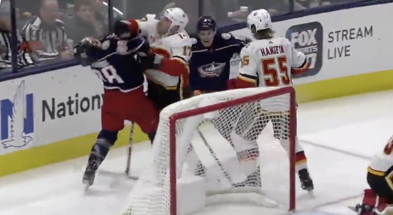 Flames forward Milan Lucic clocks Blue Jackets forward Kole Sherwood in the face after digging for a puck under David Rittich. (Twitter//BradyTrett)