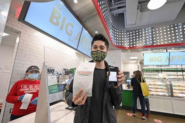 PPHOTO: Eddie Lopez shows an image of his COVID-19 vaccination card after receiving a free Krispy Kreme doughnut in New York, NY, March 30, 2021. As part of a promotion, customers can receive a free original glazed donut by showing their vaccination card. (Anthony Behar/Sipa USA via AP, FILE)