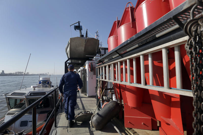 A member of the U.S. Coast Guard walks on the deck of a barge used to place navigational buoys, seen at right, along the Mississippi River to aid vessels as they travel up and down the waterway Friday, Nov. 16, 2012, in St. Louis. A top Corps of Engineers official has ordered the release of water from an upper Mississippi River reservoir in an effort to avoid closure of the river at St. Louis to barge traffic due to low water levels caused by drought. (AP Photo/Jeff Roberson)