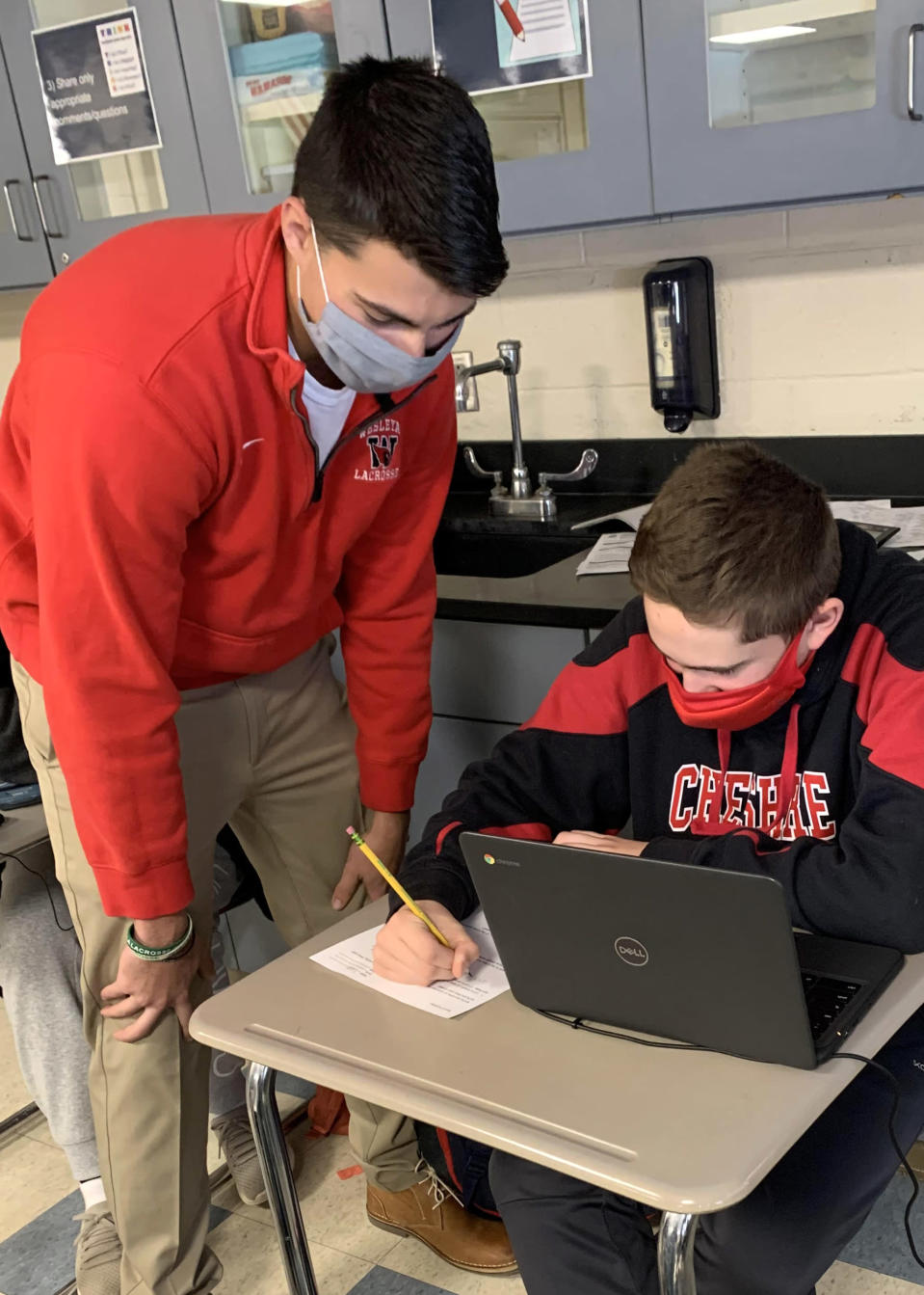 IMage: Jack Raba, a recent Cheshire Public Schools graduate, works with seventh grader Cody Persico at Dodd Middle School. Raba is one of about 50 graduates who answered the superintendent's appeal to help out by substitute teaching during the pandemic. (Courtesy of Cheshire Public Schools)