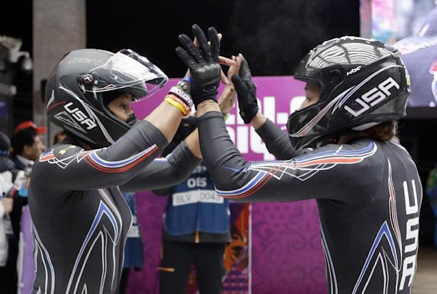 The team from the United States USA-3, piloted by Jazmine Fenlator with brakeman Lolo Jones, high five after their first run during the women's two-man bobsled competition at the 2014 Winter Olympics, Tuesday, Feb. 18, 2014, in Krasnaya Polyana, Russia. (AP Photo/Dita Alangkara)