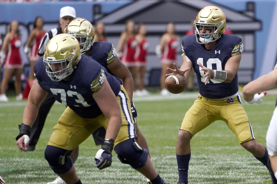 Notre Dame quarterback Drew Pyne taks a snap from center in the shotgun formation during the second half of an NCAA college football game against Wisconsin Saturday, Sept. 25, 2021, in Chicago. Notre Dame won 41-13. (AP Photo/Charles Rex Arbogast)