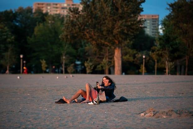 David Cohen and Alyssa Cahane have the beach to themselves on a windy and cool summer's evening at Britannia Beach in Ottawa on July 30, 2021. (Justin Tang/The Canadian Press - image credit)
