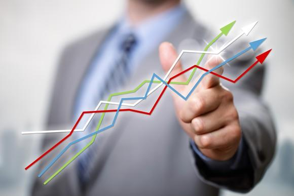 A man in a suit points to multicolored line charts going up