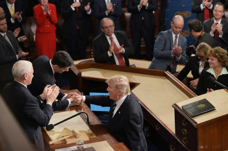 US President Donald Trump (R) shakes hands with House Speaker Paul Ryan after addressing a joint session of Congress at the US Capitol in Washington, DC on February 28, 2017