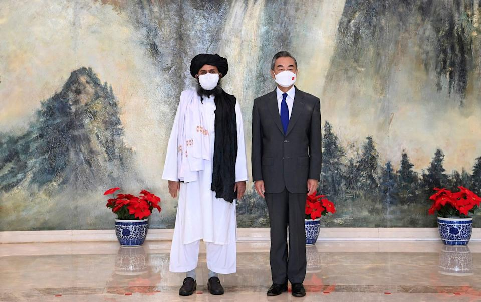 Taliban co-founder Mullah Abdul Ghani Baradar, left, and Chinese Foreign Minister Wang Yi