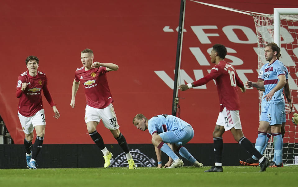 Manchester United's Scott McTominay, centre, celebrates after his team's first goal during the English Premier League soccer match between Manchester United and West Ham United at Old Trafford, Manchester, England, Sunday, March. 14, 2021. (AP Photo/Dave Thompson,Pool)