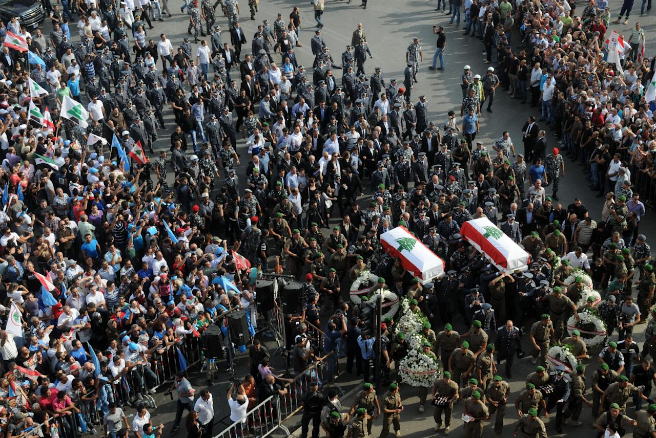 Lebanese honor guards carry the flag-draped coffins of Brig. Gen. Wissam al-Hassan and his bodyguard Ahmad Sahyouni who were assassinated on Friday by a car bomb, during their funeral procession at Martyrs' Square in Beirut, Lebanon, Sunday Oct. 21, 2012. Lebanese soldiers fired guns and tear gas to push back hundreds of protesters who broke through a police cordon and tried to storm the government headquarters in Beirut. The enraged crowd came from the funeral of a top Lebanese intelligence official assassinated in a massive car bombing.(AP Photo/Ahmad Omar)