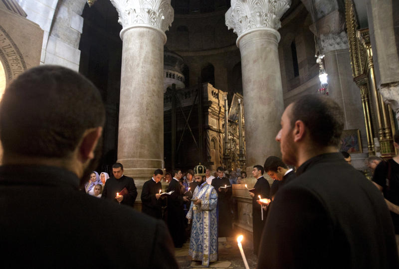 Christian clergymen hold candles inside the Church of the Holy Sepulchre, in Jerusalem's Old City, Friday, Nov. 2, 2012. A clergyman from the church built on the site where Jesus Christ is said to have been crucified said Friday that its bank account has been frozen as the result of a long-standing dispute with an Israeli water company. (AP Photo/Sebastian Scheiner)