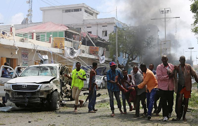 <p>Rescuers assist injured men from the scene of an explosion near Wehliye Hotel on Maka al Mukaram street in Somalia's capital Mogadishu, March 13, 2017. (Feisal Omar/Reuters) </p>