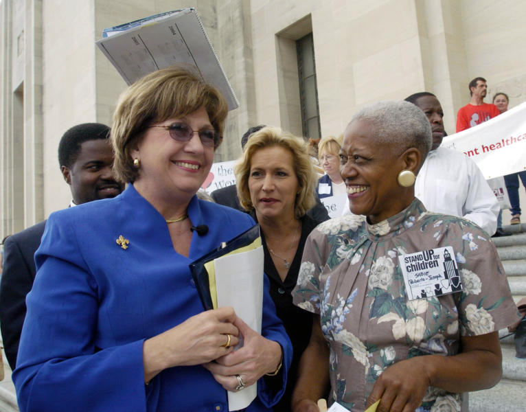 FILE - In this April 20, 2004 file photo, Rep. Carla Blanchard Dartez, D-Morgan City, center covers Gov. Kathleen Blanco, left, as a few drops of rain fall while talking with Sadie Roberts-Joseph, right, before the start of the Stand Up for Children 2004 Rally for Children on the steps of the State Capitol in Baton Rouge, La. Sadie Roberts-Joseph, who founded an African American history museum was discovered dead in the trunk of a car, and police said Saturday, July 13, 2019 that investigators were working diligently to find those responsible.(Arthur D. Lauck/The Advocate via AP, File)