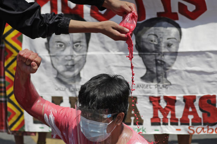 A protester pours red paint on another to symbolize killings as they hold a rally outside the Malacanang palace in Manila, Philippines on Wednesday, June 30, 2021. The group has called for justice and accountability for the thousands who have died due to the government's anti-drug crackdown under the Duterte administration. (AP Photo/Aaron Favila)