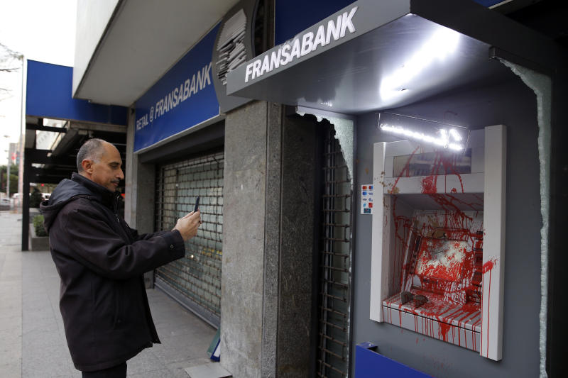 A man uses his phone to take a picture of ATM screen of Fransa Bank that was painted and damaged by anti-government protesters in Beirut, Lebanon, Wednesday, Jan. 15, 2020. Banks in Hamra trade street were badly damaged after a night that witnessed clashes between anti-government protesters and Lebanese riot police. (AP Photo/Bilal Hussein)