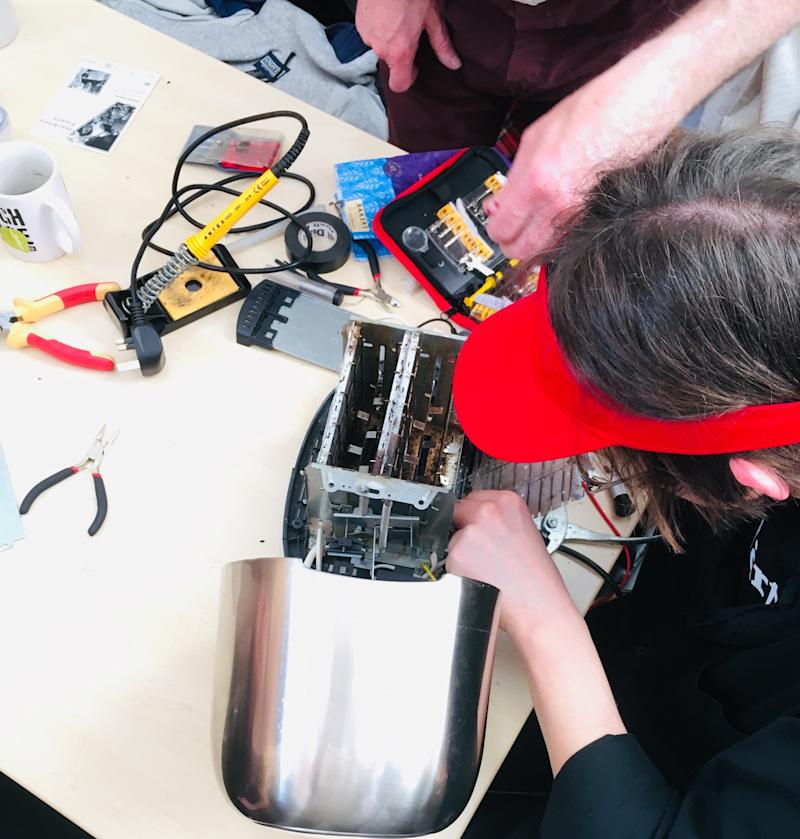 """A volunteer """"fixpert"""" assesses a broken toaster at the repair event I went to in London. The aim isn't just to fix the appliance but to share repair skills and confidence with its owner. (Tess Riley for HuffPost)"""