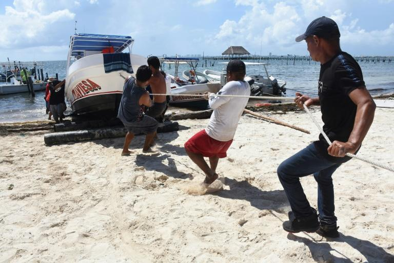 Fishermen and tour operators haul their boats onto dry land as a hurricane approaches Mexico's Caribbean coast