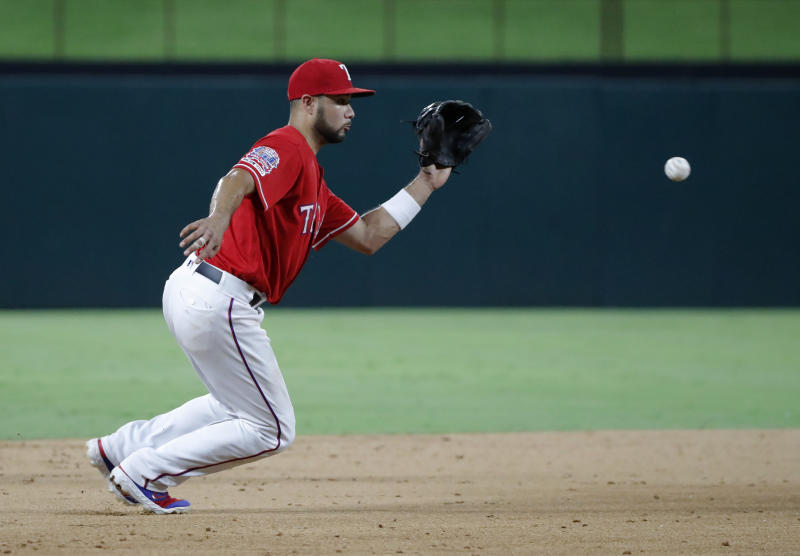 Texas Rangers third baseman Isiah Kiner-Falefa reaches to field a groundout by Los Angeles Angels' Wilfredo Tovar in the sixth inning of baseball game in Arlington, Texas, Monday, Aug. 19, 2019. (AP Photo/Tony Gutierrez)