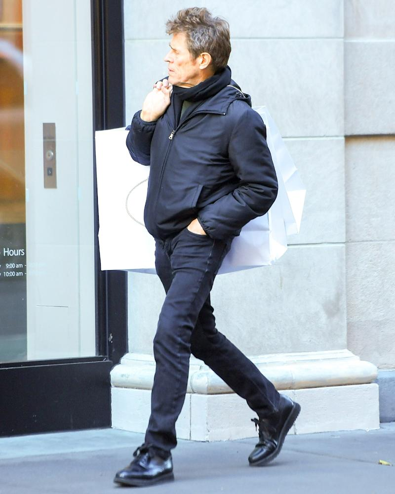 Willem Dafoe carries home two bags' worth of more #BigFitoftheDay ammo from Prada.