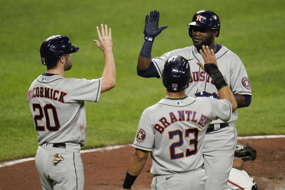 Houston Astros' Yordan Alvarez, top right, is greeted near home plate after he drove in Chas McCormick (20) and Michael Brantley (23) on a three-run home run off Baltimore Orioles starting pitcher Keegan Akin during the third inning of a baseball game, Monday, June 21, 2021, in Baltimore. (AP Photo/Julio Cortez)