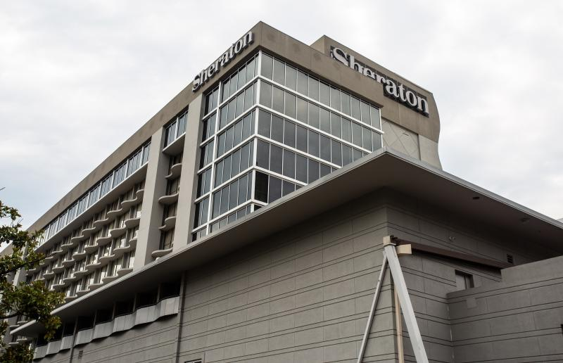 "FILE-In this Wednesday, July 31, 2019 file photo, the entrance to the Sheraton Atlanta Hotel is seen, in Atlanta. A lawsuit alleges ""negligence in the operation and maintenance of the water systems"" caused a Legionnaires' disease outbreak at a downtown Atlanta hotel. The lawsuit was filed Monday in Gwinnett County State Court by Germany Greer, who says he tested positive for the disease after attending a conference at the Sheraton Atlanta Hotel June 27-July 1. (AP Photo/Ron Harris, File)"