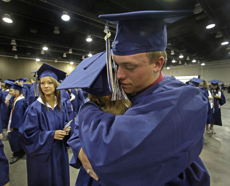 Southmoore High School senior Jake Spradling, hugs a classmate as they get ready to attend their commencement ceremony in Oklahoma City Saturday, May 25, 2013, five days after a tornado destroyed a large swath of their attendance area in Moore, Okla. Spradling's home was among those destroyed after a huge tornado roared through the Oklahoma City suburb Monday, flattening a wide swath of homes and businesses. (AP Photo/Charlie Riedel)