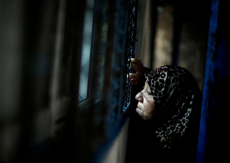 FILE PHOTO: A Palestinian refugee woman waits to receive food supplies from a United Nations food distribution center in Al-Shati refugee camp in Gaza City December 6, 2017. REUTERS/Mohammed Salem/File Photo