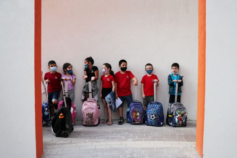 Pupils, wearing protective face masks, stand together upon arrival at their school as Israel reopens first to fourth grades, continuing to ease a second nationwide coronavirus disease (COVID-19) lockdown, at a school in Rehovot
