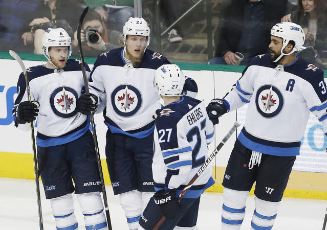 Winnipeg Jets forward Patrik Laine (29), second form left, is congratulated by teammates after scoring a goal during the second period of an NHL hockey game against the Dallas Stars, Saturday, Feb. 24, 2018, in Dallas. (AP Photo/Brandon Wade)