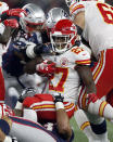 Kansas City Chiefs running back Kareem Hunt (27) is tackled by New England Patriots defenders during the first half of an NFL football game, Sunday, Oct. 14, 2018, in Foxborough, Mass. (AP Photo/Michael Dwyer)