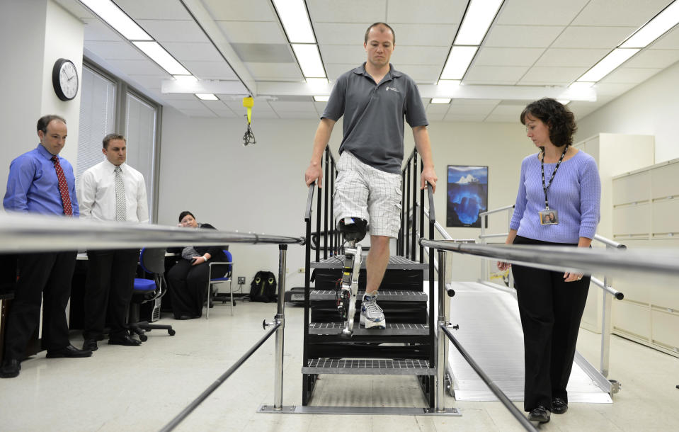 """In this Oct. 25, 2012 photo, physical therapist assistant Suzanne Finucane, right, helps Zac Vawter as he practices walking with an experimental """"bionic"""" leg at the Rehabilitation Institute of Chicago. After losing his right leg in a motorcycle accident, the 31-year-old software engineer signed up to become a research subject, helping test a trailblazing prosthetic leg that's controlled by his thoughts. He will put this leg to the ultimate test Sunday, Nov. 4 when he attempts to climb 103 flights of stairs to the top of Chicago's Willis Tower, one of the world's tallest skyscrapers. (AP Photo/Brian Kersey)"""