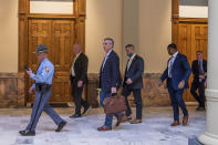 Lead by a Georgia State Trooper, Georgia Secretary of State Brad Raffensperger, center, exits the Georgia State Capitol building after hearing reports of threats, Wednesday, Jan. 6, 2021, in Atlanta. (Alyssa Pointer/Atlanta Journal-Constitution via AP)