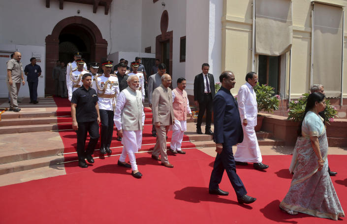 Indian President Ram Nath Kovind, center, accompanied by Indian Prime Minister Narendra Modi, left arrives to address joint session of Parliament in New Delhi, India, Thursday, June 20, 2019. India's government has created a new ministry to grapple with a growing water crisis, with more than 60% of the country's 1.3 billion people dependent on farming and good monsoon rains, Kovind told Parliament on Thursday. (AP Photo)