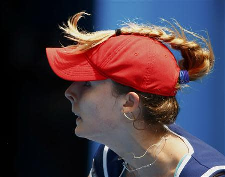 Alize Cornet of France's plait is seen on top of the cap she is wearing as she plays a shot to Maria Sharapova of Russia during their women's singles match at the Australian Open 2014 tennis tournament in Melbourne January 18, 2014. REUTERS/David Gray