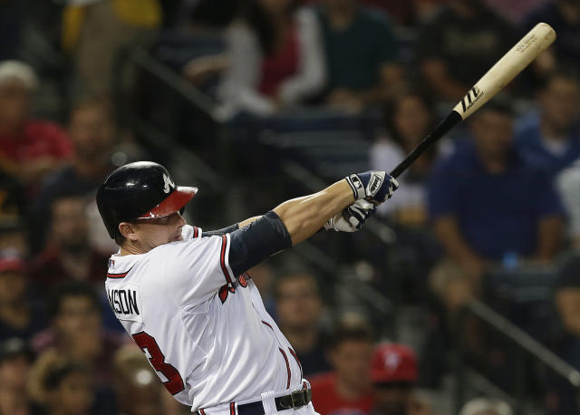 Atlanta Braves third baseman Chris Johnson (23) follows through with a two-run base hit in the second inning of a baseball game against the Philadelphia Phillies in Atlanta, Wednesday, Aug. 14, 2013. (AP Photo/John Bazemore)