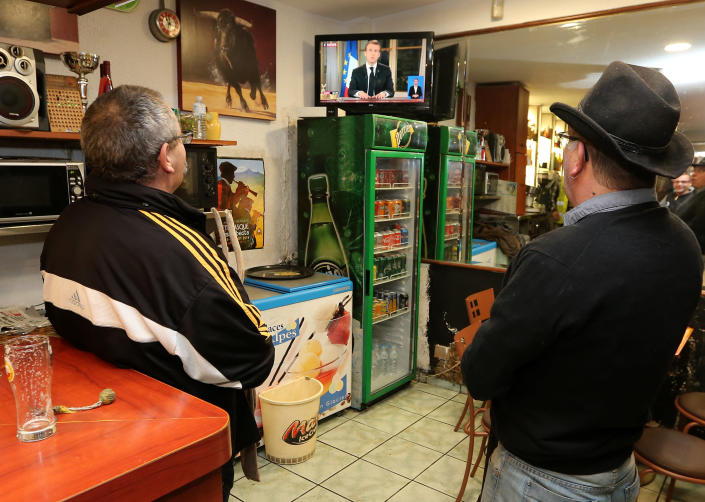 People watch French President Emmanuel Macron during a televised address to the nation, in Hendaye, southwestern France, Monday, Dec. 10, 2018. In an unusual admission, French President Emmanuel Macron says he's partially responsible for anger fueling protests. (AP Photo/Bob Edme)