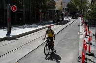 A man rides his bike by an almost empty area of the city following the implementation of stricter social-distancing and self-isolation rules to limit the spread of the coronavirus disease (COVID-19) in Sydney