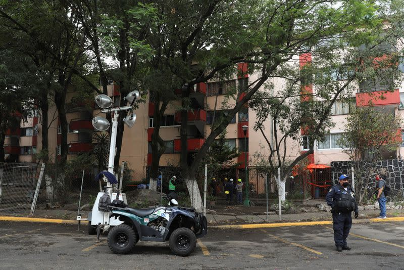 A police officer stands guard as members of Civil Protection check an apartment building damaged by an earthquake that struck southern Mexico on Tuesday, in Mexico City