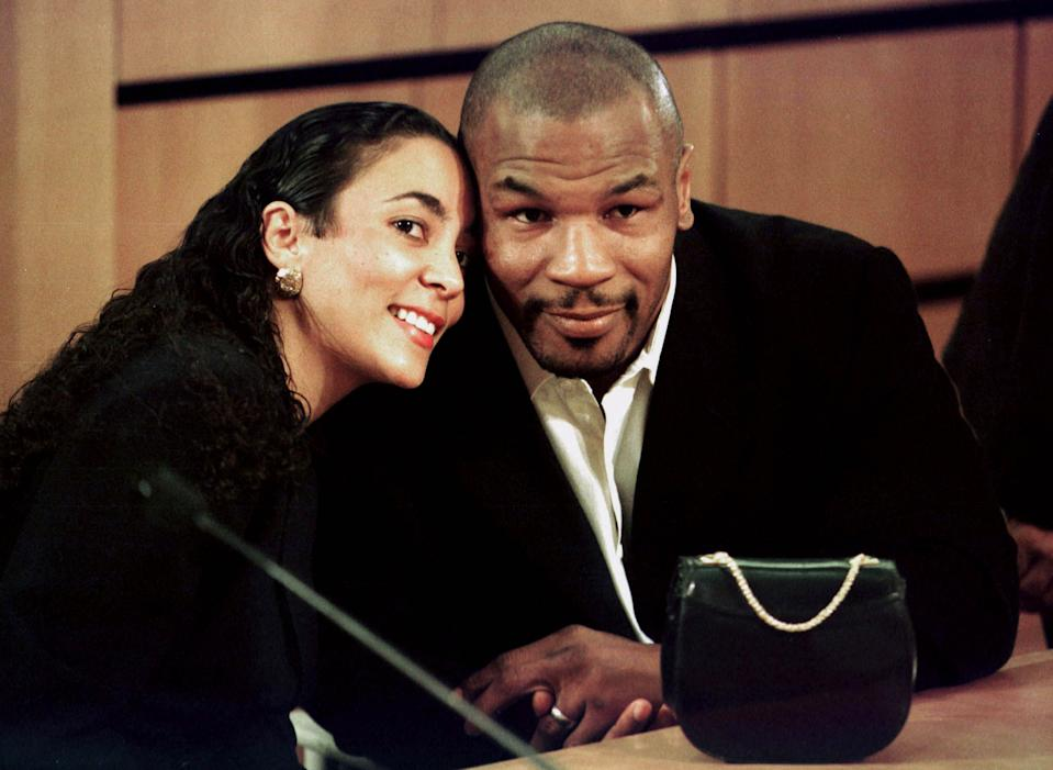 Boxer Mike Tyson poses for photographers with his wife Monica Turner Tyson before the start of his succesful re-licensing hearing before the Nevada State Athletic Commission at the Clark County Government Center October 19, in Las Vegas. [Tyson had his license revoked for biting the ears of Evander Holyfield in a heavyweight  title fight  June 28, 1997, but it was reinstated today, ending a suspension that lasted almost 16 months. ]