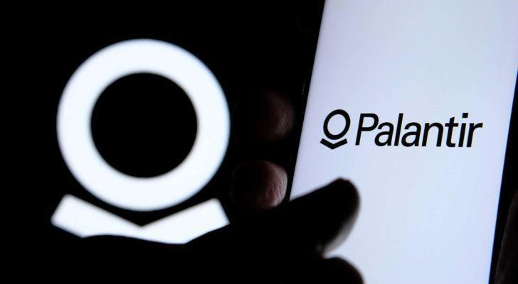 A close-up shot of a hand on a screen with the Palantir (PLTR) logo.